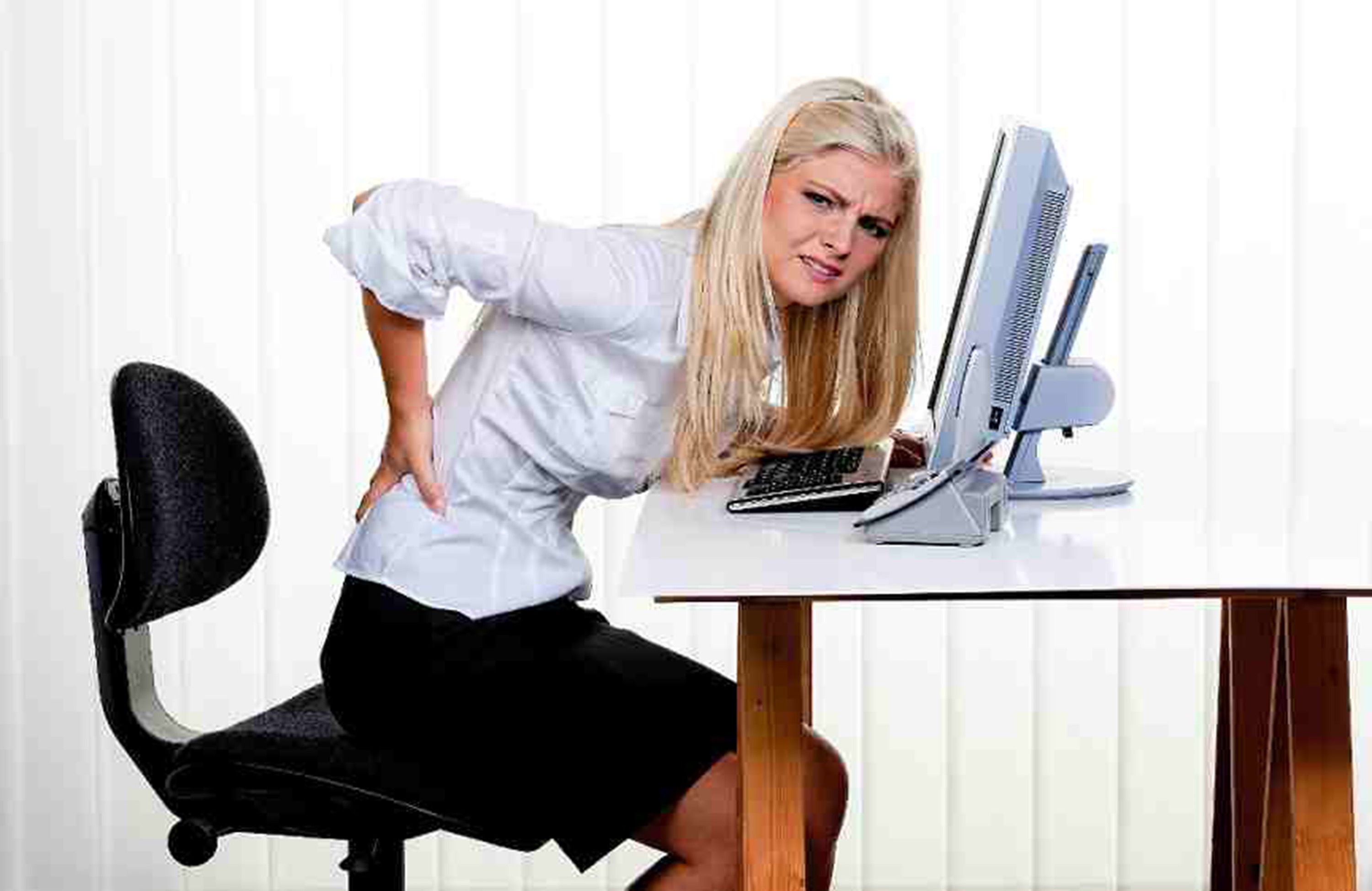 woman with back pain at desk
